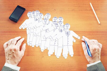 duplicate: Concept of team building. Abstract image with a man making human characters on the table