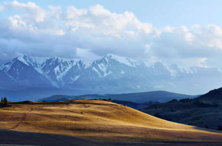 mountaintops: Beautiful evening landscape with sunny valley and snowy mountains in the distance Stock Photo