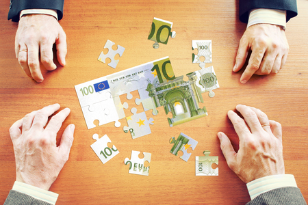 gather: Businessmen gather One hundred Euros as a set of puzzles on the wooden desk