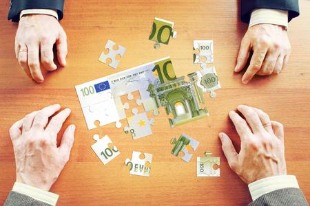 recolectar: Los hombres de negocios se re�nen cien euros como un conjunto de rompecabezas sobre la mesa de madera