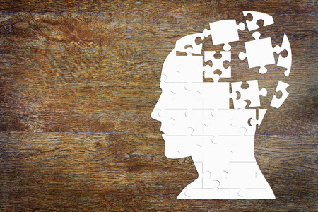 man head: Human head as a set of puzzles on the wooden background Stock Photo