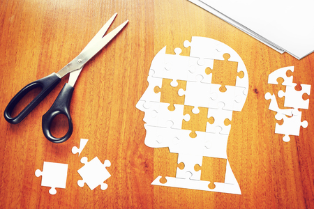 psychics: Human head as a set of puzzles on the wooden desk Stock Photo