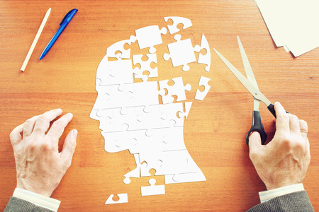 psych: Man gathers a human head as puzzles on the wooden desk Stock Photo