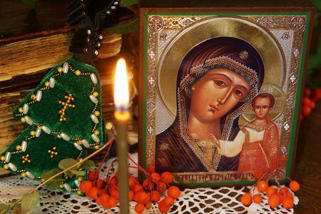 virgen maria: Ortodoxa religiosa sigue la vida con un icono de la Santa Madre y vela encendida Foto de archivo