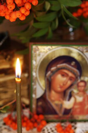 Mother Mary: Religious still life with burning candle and an icon of the Mother Mary (focus on the candle)