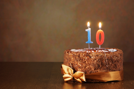 ten: Birthday chocolate cake with burning candle as a number ten on brown background Stock Photo