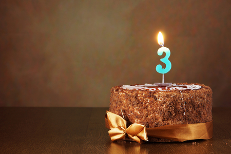 Birthday chocolate cake with burning candle as a number three on brown background
