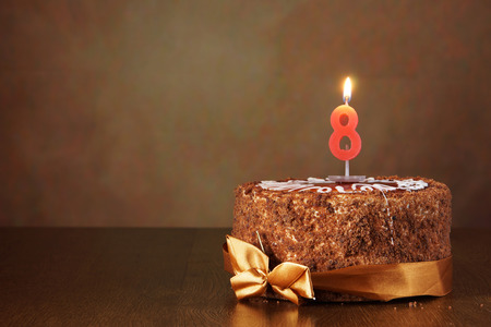 Birthday chocolate cake with burning candle as a number eight on brown background Foto de archivo