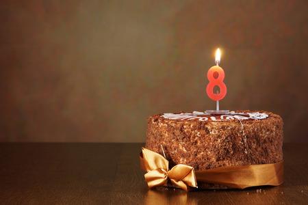 pastel de chocolate: Torta de cumplea�os de chocolate con velas encendidas como n�mero ocho en fondo marr�n Foto de archivo