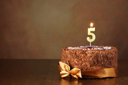 Birthday chocolate cake with burning candle as a number five on brown background