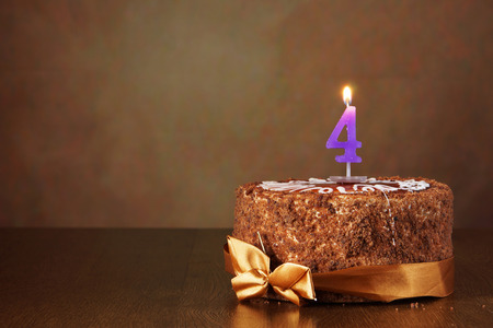 Birthday chocolate cake with burning candle as a number four on brown background