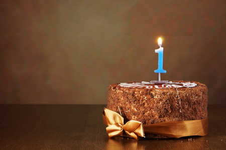 Birthday chocolate cake with burning candle as a number one on brown background