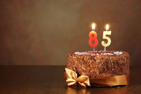 eighty: Birthday chocolate cake with burning candles as a number eighty five on brown background