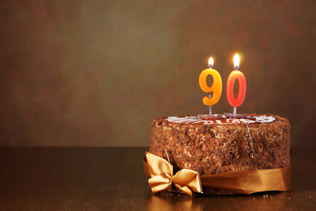 ninety: Birthday chocolate cake with burning candles as a number ninety on brown background