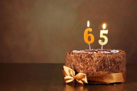 sixty: Birthday chocolate cake with burning candles as a number sixty five on brown background