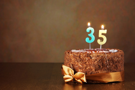 thirty five: Birthday chocolate cake with burning candles as a number thirty five on brown background