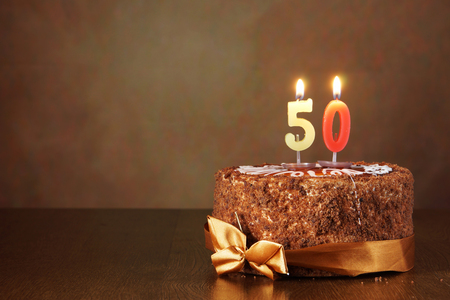 Birthday chocolate cake with burning candles as a number fifty on brown background