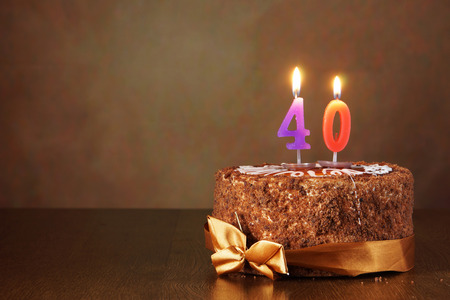 forty: Birthday chocolate cake with burning candles as a number forty on brown background Stock Photo