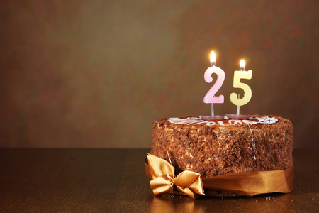 Birthday chocolate cake with burning candles as a number twenty five on brown background