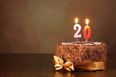 Birthday chocolate cake with burning candles as a number twenty on brown background 스톡 콘텐츠
