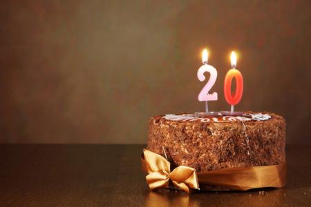 tortas de cumpleaños: Pastel de chocolate de cumpleaños con velas encendidas como un número veinte en fondo marrón