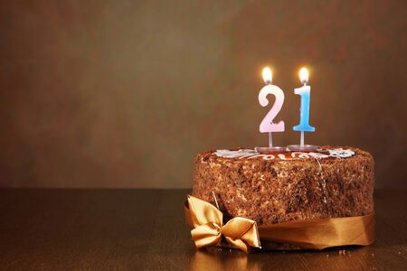 twenty one: Birthday chocolate cake with burning candles as a number twenty one on brown background Stock Photo