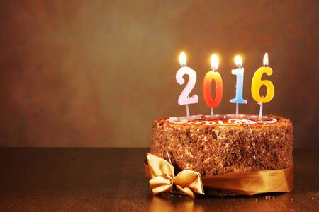 New Year 2016 still life. Chocolate cake and burning candles on brown background
