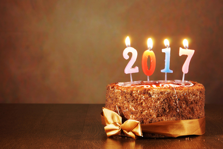 sweet seventeen: New Year 2017 still life. Chocolate cake and burning candles on brown background