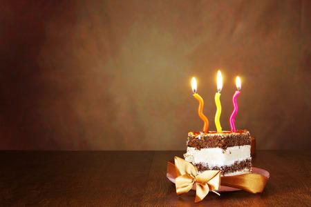 porcion de torta: Pedazo de pastel de chocolate de cumpleaños con velas encendidas contra fondo marrón Foto de archivo