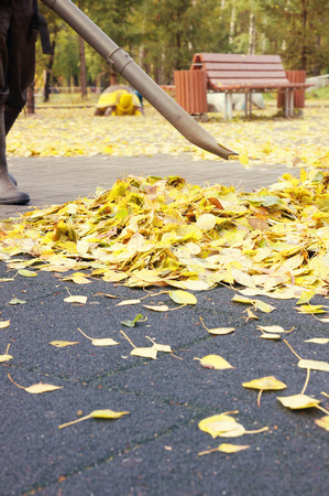 gardening: Worker removing dead leaves from the playground with a gasoline blower in the autumn park