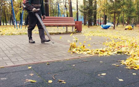 Worker cleaning playground in the autumn park from dead leaves with a blower