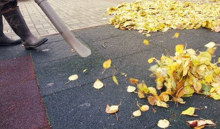 gardening: Worker cleaning ground in the autumn park from dead leaves with a blower