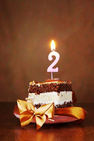 pastel cumpleaños: Pedazo de torta de cumpleaños de chocolate con la vela ardiente como el número dos en el fondo de Brown Foto de archivo