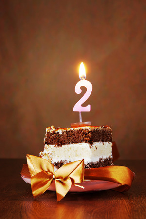 Piece of Birthday Chocolate Cake with Burning Candle as a Number Two on Brown Background