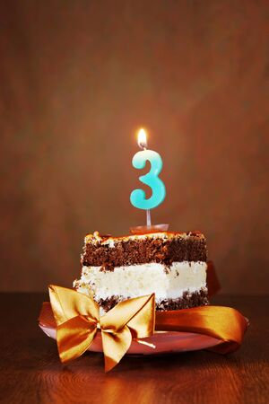 anniversary: Piece of Birthday Chocolate Cake with Burning Candle as a Number Three on Brown Background