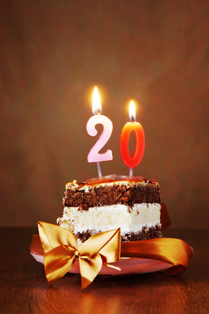 Piece of Birthday Chocolate Cake with Burning Candle as a Number Twenty on Brown Background