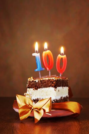 Piece of Birthday Chocolate Cake with Burning Candle as a Number One Hundred on Brown Background 免版税图像