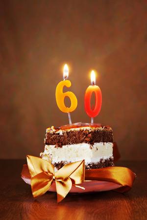 vejez feliz: Pedazo de pastel de chocolate de cumplea�os con vela encendida y un n�mero sesenta en el fondo de Brown