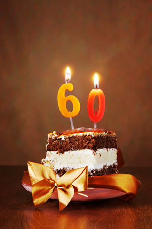 Piece of Birthday Chocolate Cake with Burning Candle as a Number Sixty on Brown Background Stock Photo