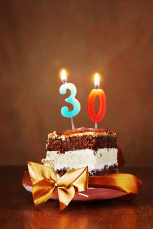 happy life: Piece of Birthday Chocolate Cake with Burning Candle as a Number Thirty on Brown Background Stock Photo