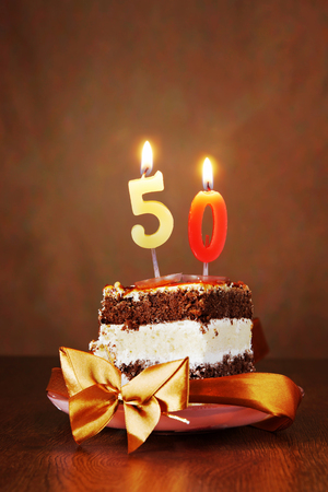 Piece of Birthday Chocolate Cake with Burning Candle as a Number Fifty on Brown Background Stock Photo