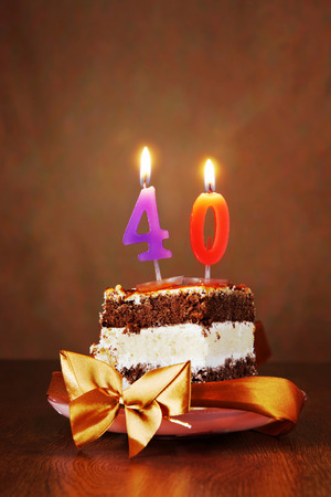 Piece of Birthday Chocolate Cake with Burning Candle as a Number Forty on Brown Background