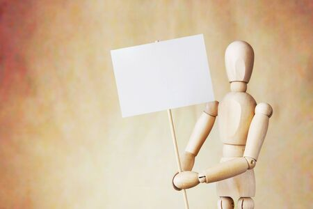 marioneta de madera: Wooden puppet holding blank white poster in its hands. Conceptual image about claims Foto de archivo