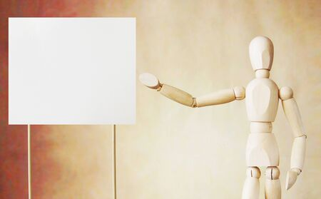 broadsheet: Wooden puppet points to blank white broadsheet with its hand. Conceptual image about presentation Stock Photo