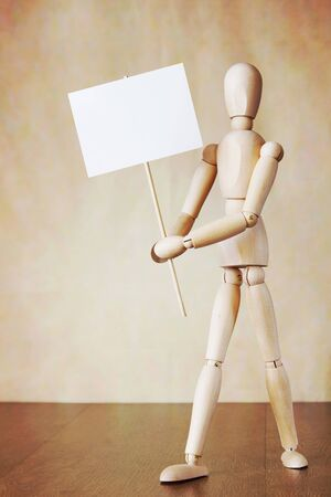 declare: Wooden human model holding blank white poster. Concept of demands Stock Photo