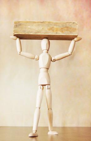 marioneta de madera: Hombre que lleva una carga pesada sobre su cabeza. Imagen abstracta con una marioneta de madera Foto de archivo