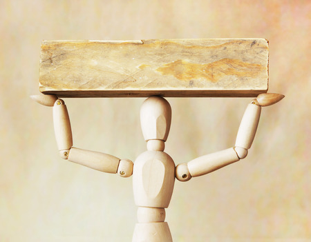 Man bearing heavy load over its head. Abstract image with a wooden puppet