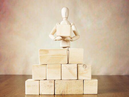 marioneta de madera: El hombre la construcción de un muro de grandes bloques. Imagen conceptual con la marioneta de madera Foto de archivo