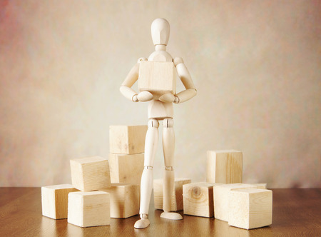 Man stands among blocks and holds the one. Conceptual image with wooden puppet