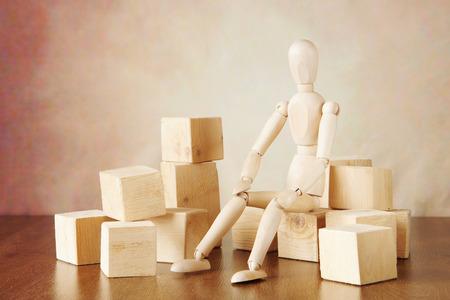 marioneta de madera: El hombre se sienta cuidadosamente entre los grandes bloques. Imagen conceptual con la marioneta de madera